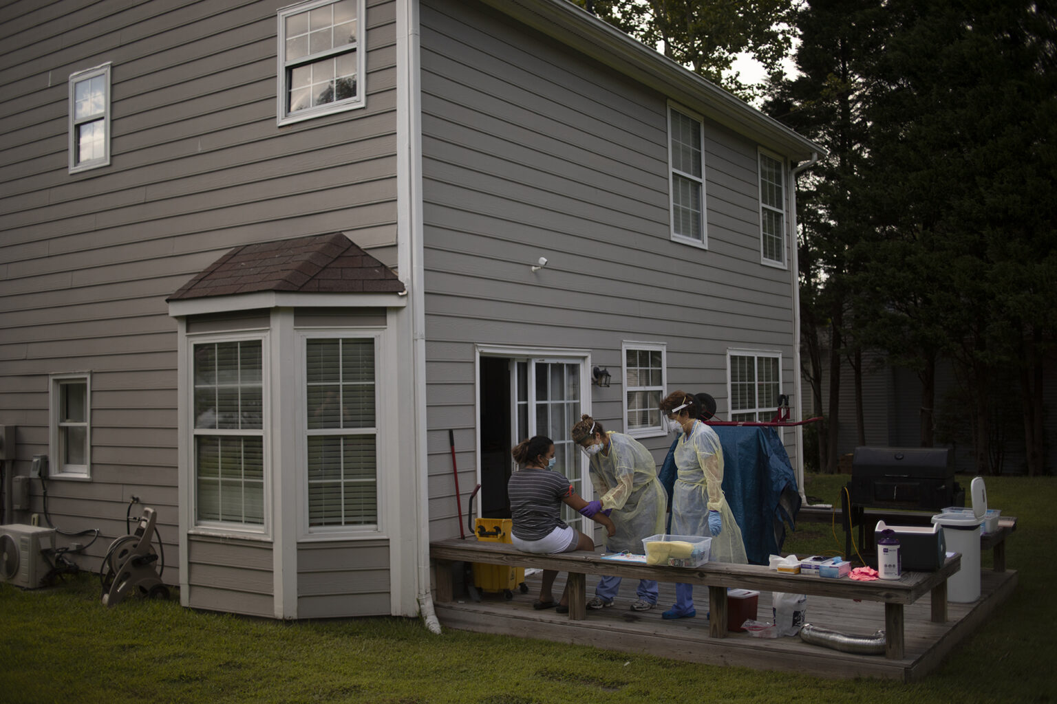 Researchers take samples from a patient outside their home.
