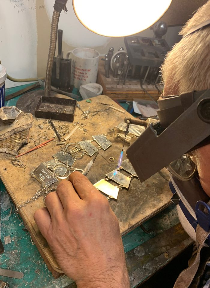 A silversmith adds a plate to a chain.