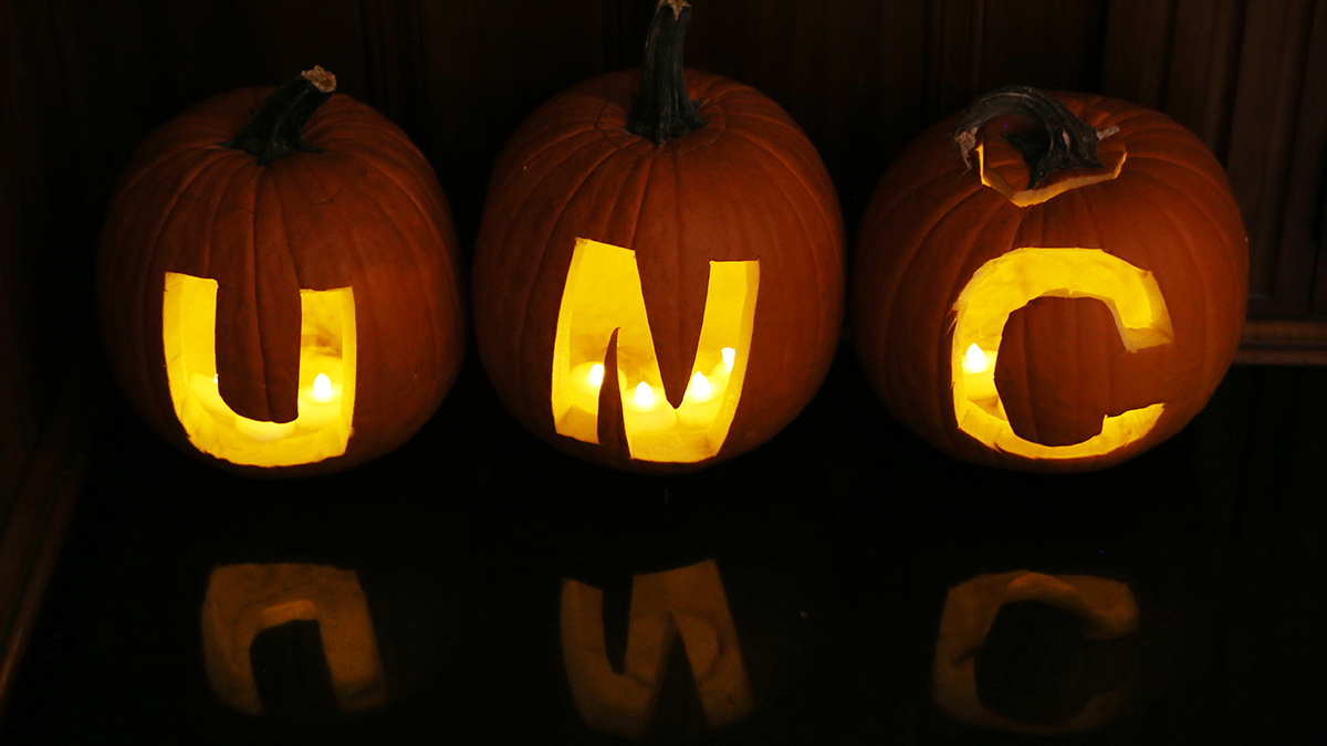 Three pumpkins with UNC carved in them.