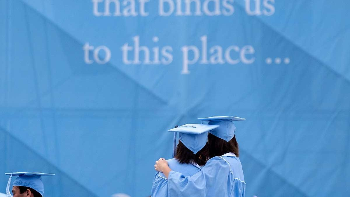 Students hug at commencement.