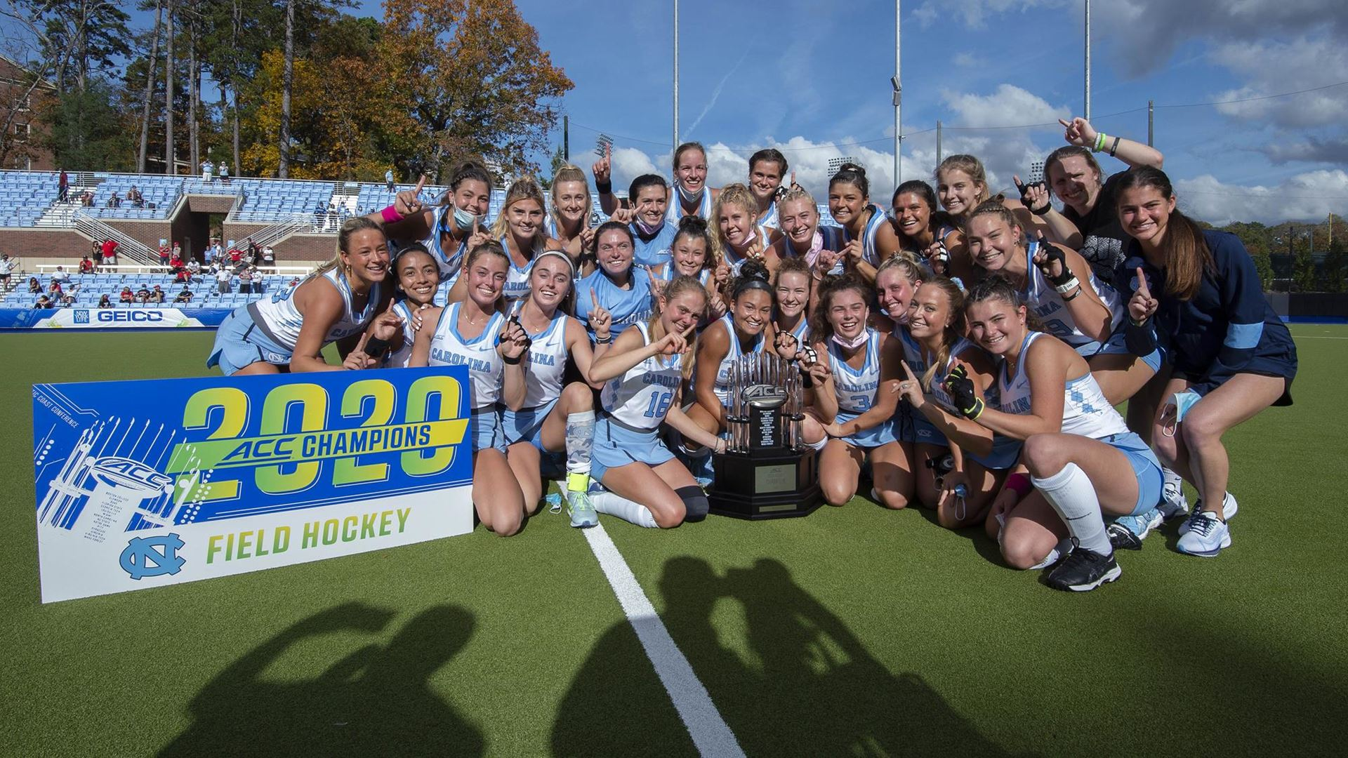 The Field hockey team celebrates with a 2020 championship banner.