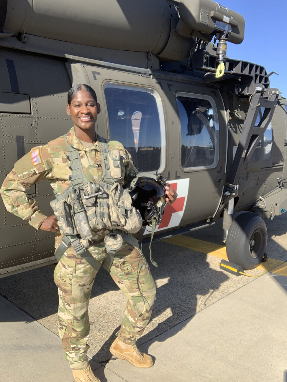 Lindsey Jefferies in uniform, smiles in front of a Black Hawk medical helicopter.