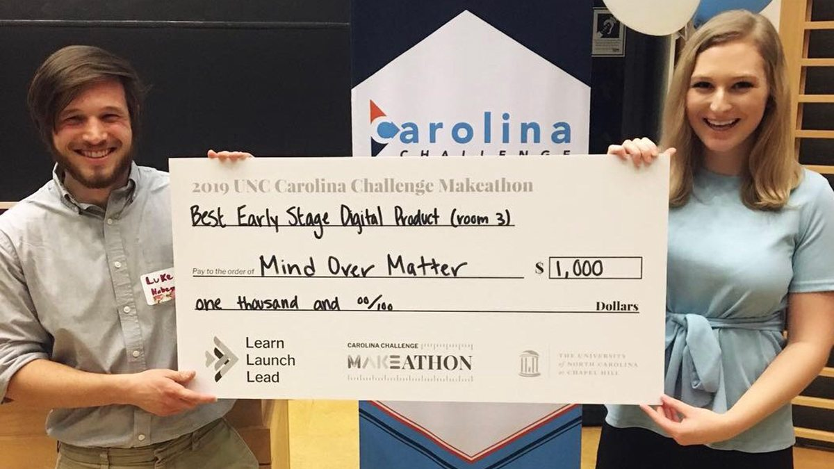 Luke Habegger and Megan Schneider hold a large check they won in a pitch competition.