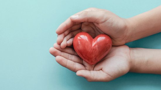 A hand holding a ceremic heart.