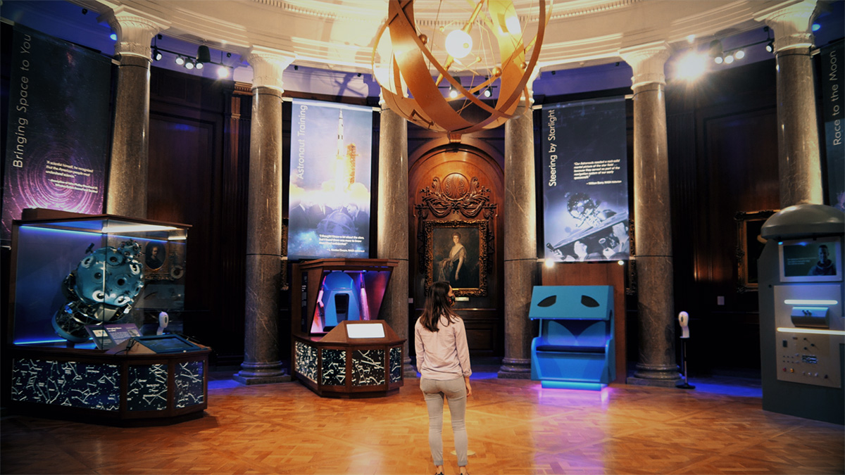A person stands in the lobby of Morehead Planetarium and Science Center.