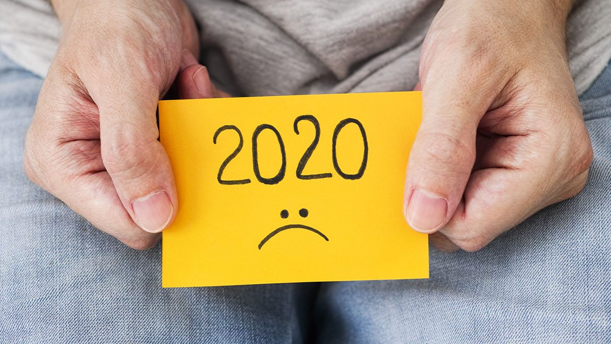 A person holds a post-it note with 2020 and a sad face drawn on it.