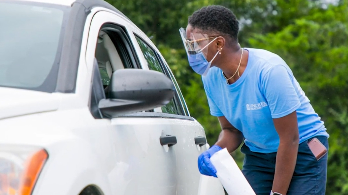 A health care worker talks to a person in a car.