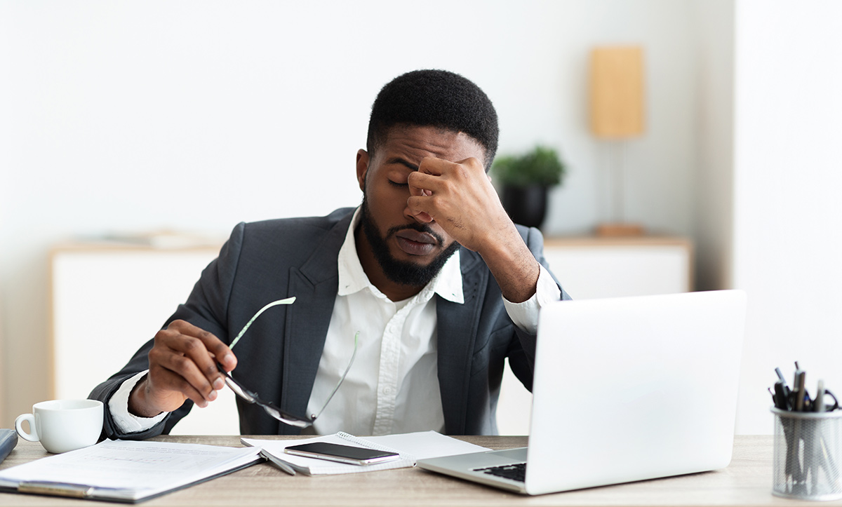 A man looks stressed at his computer.