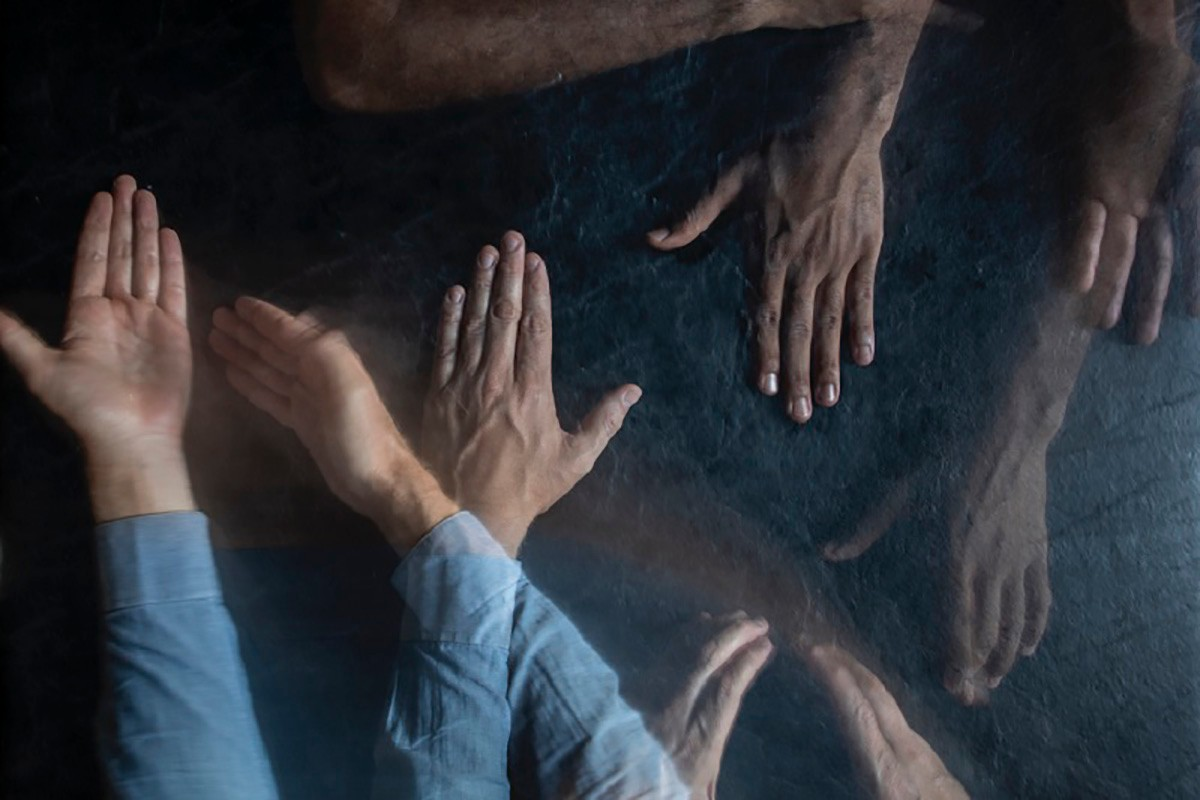 Many hands move across a dark background.