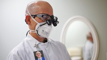 A dentist wears the AerFrame over his N95 mask.