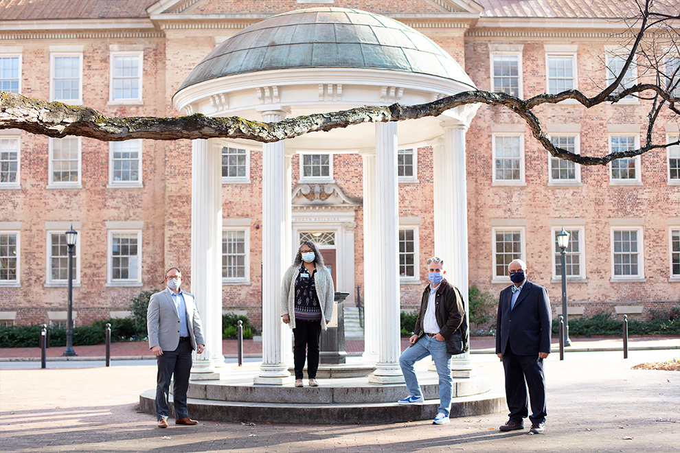 Four professors stand near the Old Well.