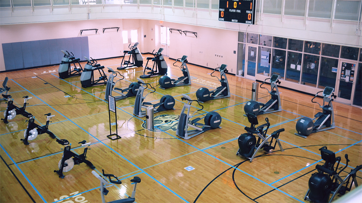 A basketball court with cardio workout equipment spread out.
