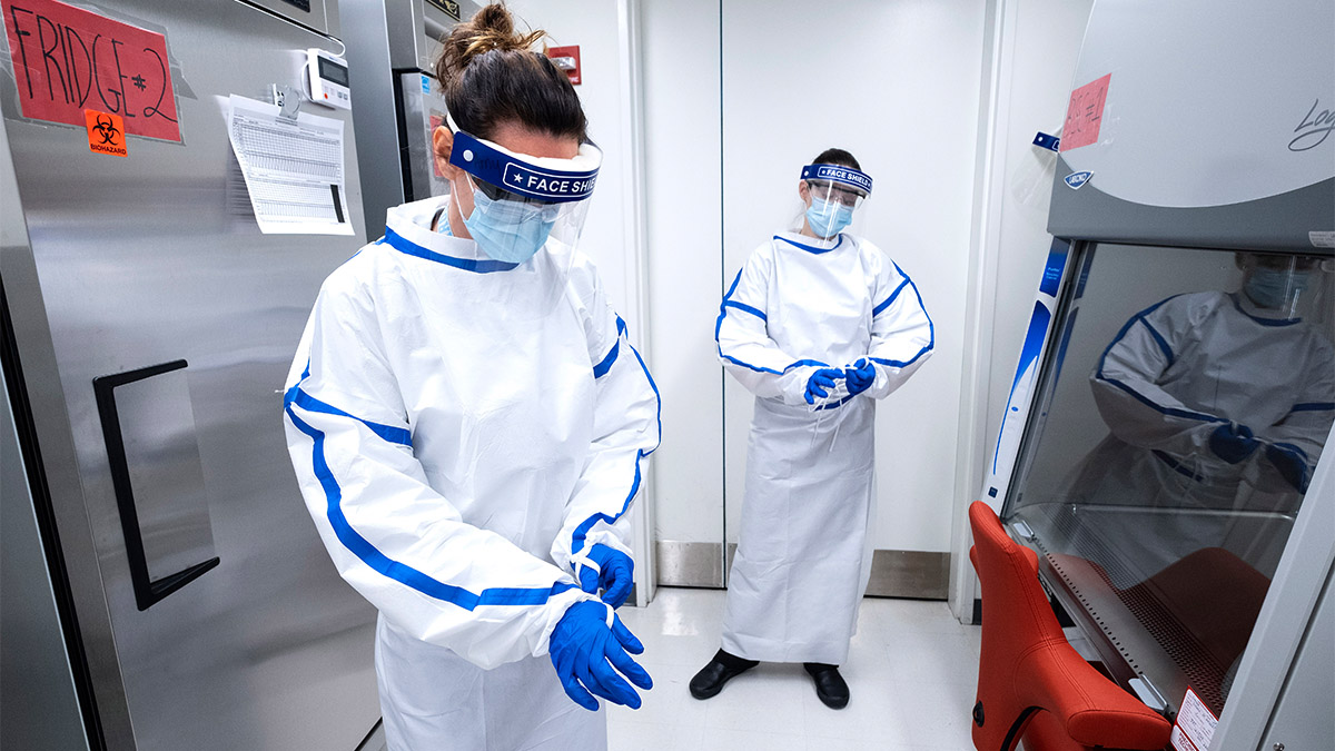 Two researchers in white lab gear work in a covid-19 testing lab.