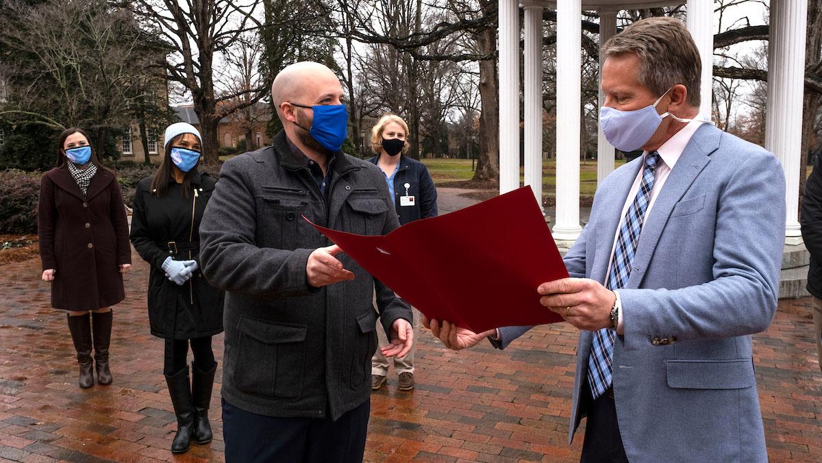 Garret Reid hands a certificate to Chancellor Guskiewicz.