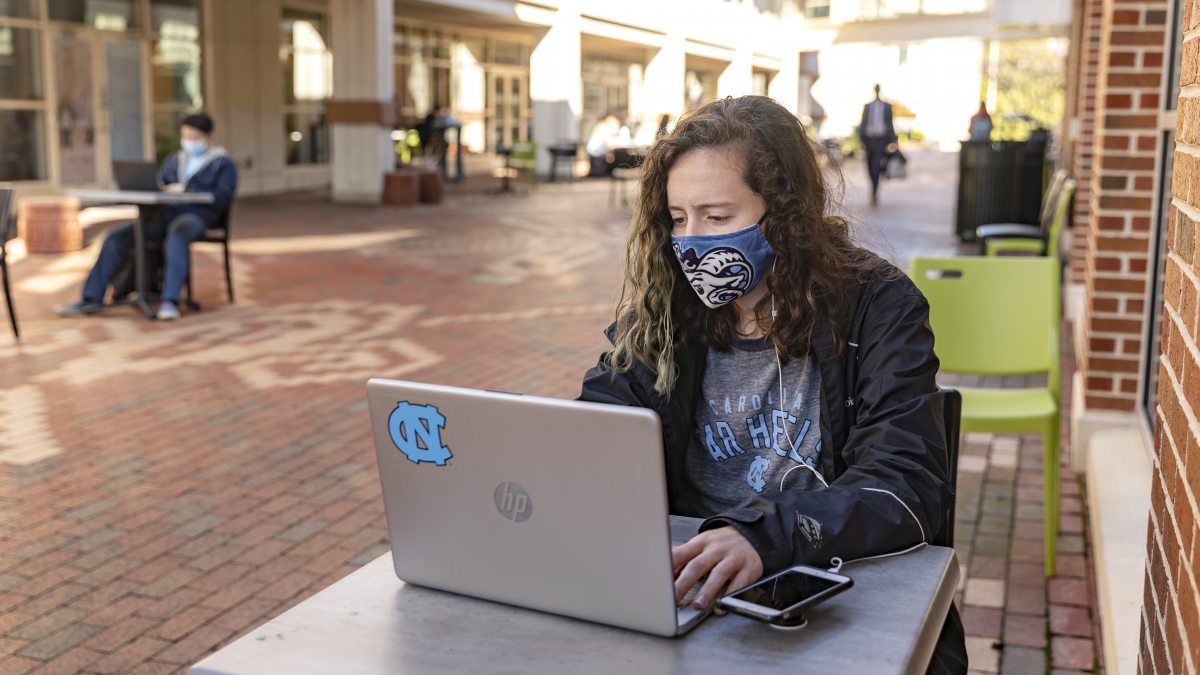 A student works on a laptop near the Carolina Union.