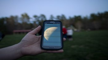 A hand holds a cell phone with the picture of a moon on it.