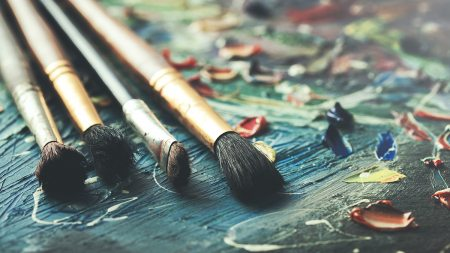 Paint brushes resting on a table with paint.