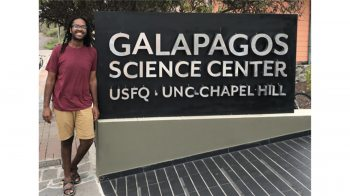 Khristopher Nicholas stands near a sign at the Galapagos Science Center.