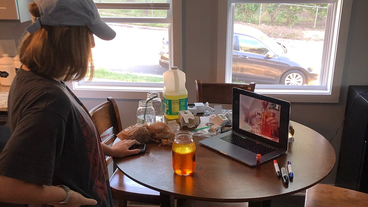 A student puts food coloring into a cup of water on a zoom call.