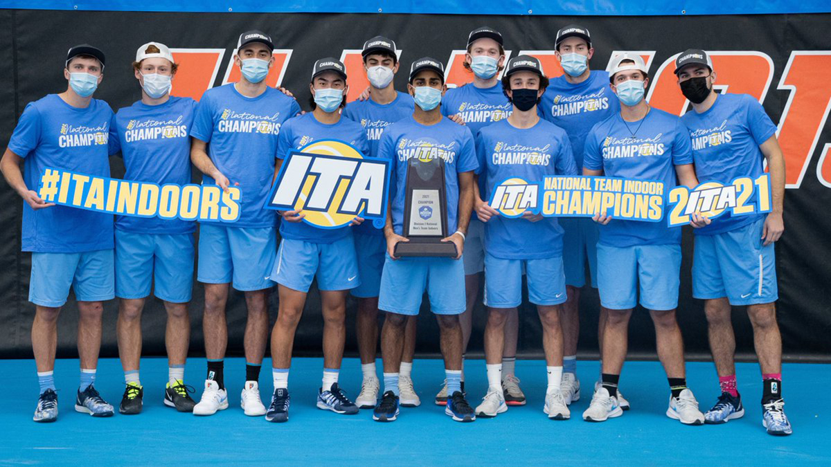 Members of the men's tennis team hold a ITA trophy.
