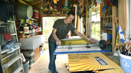 Bob Goldstein working on a screenprinting press in a shed.