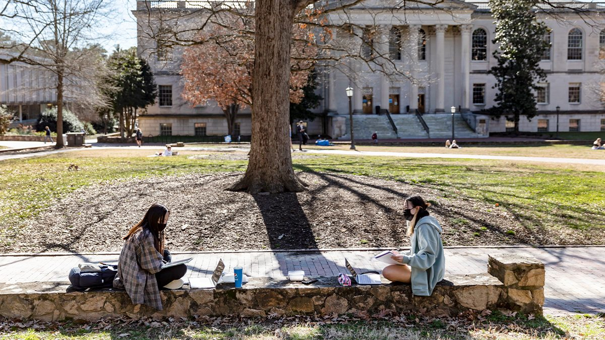 Two students sit on a stone wall working.