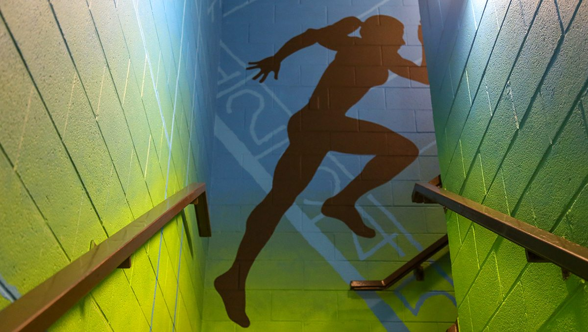 A mural of a person running in a stairwell.