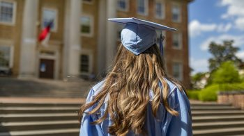 A graduate in a cap and gown stands near South Building.