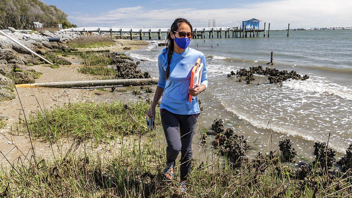 A woman walks along the coastline in Morehead City, North Carolina.