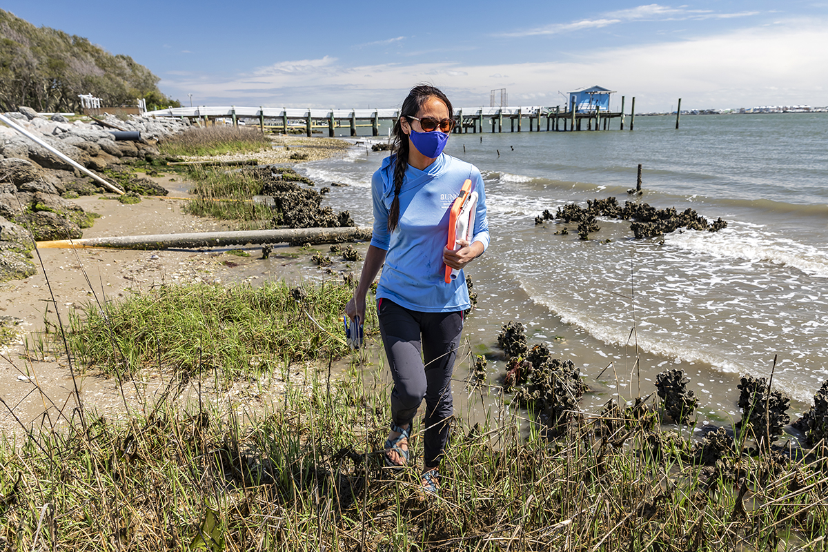 A woman walks along the coastline in Morehead City, North Carolina.