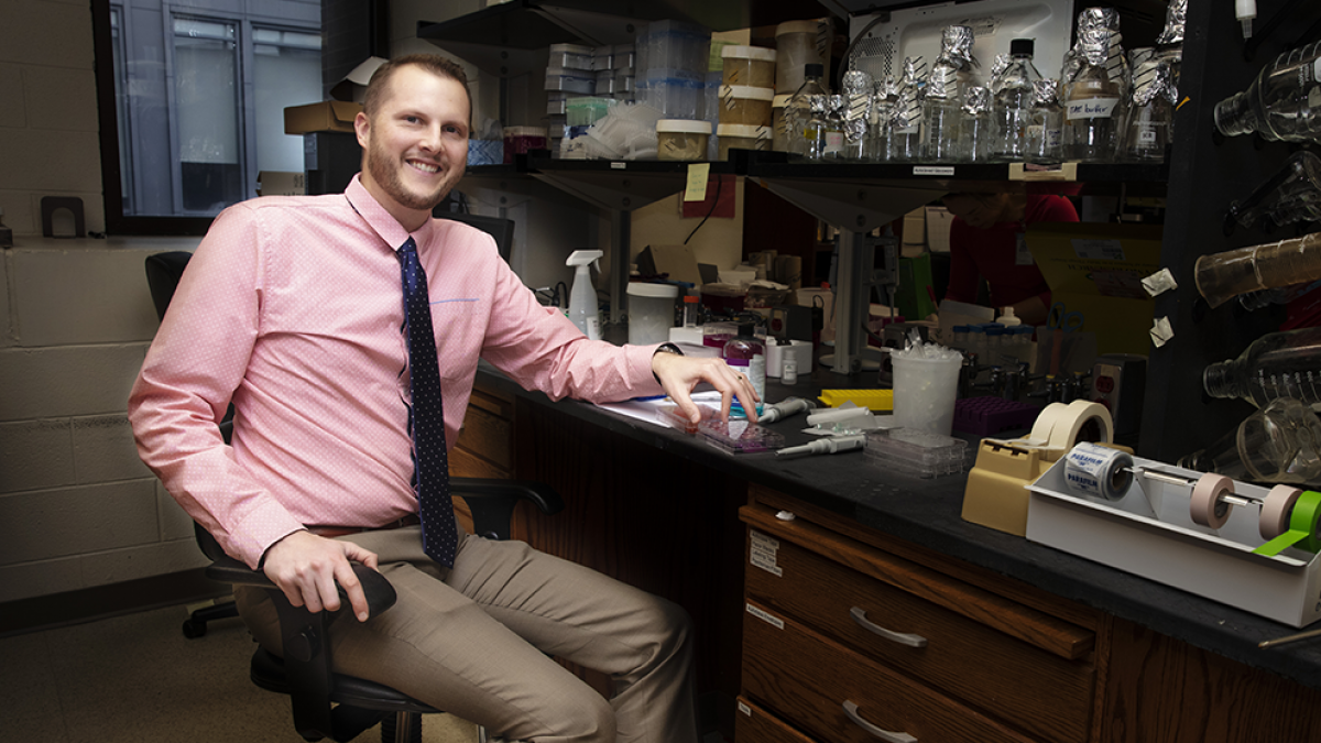 Chad Pecot sits near a lab bench.