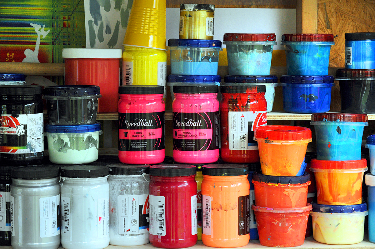 Containers of paint on a shelf.