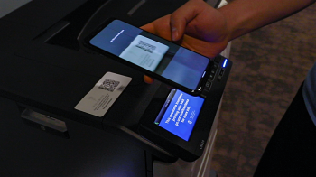 A person holds a cell phone above a printer to scan a code.