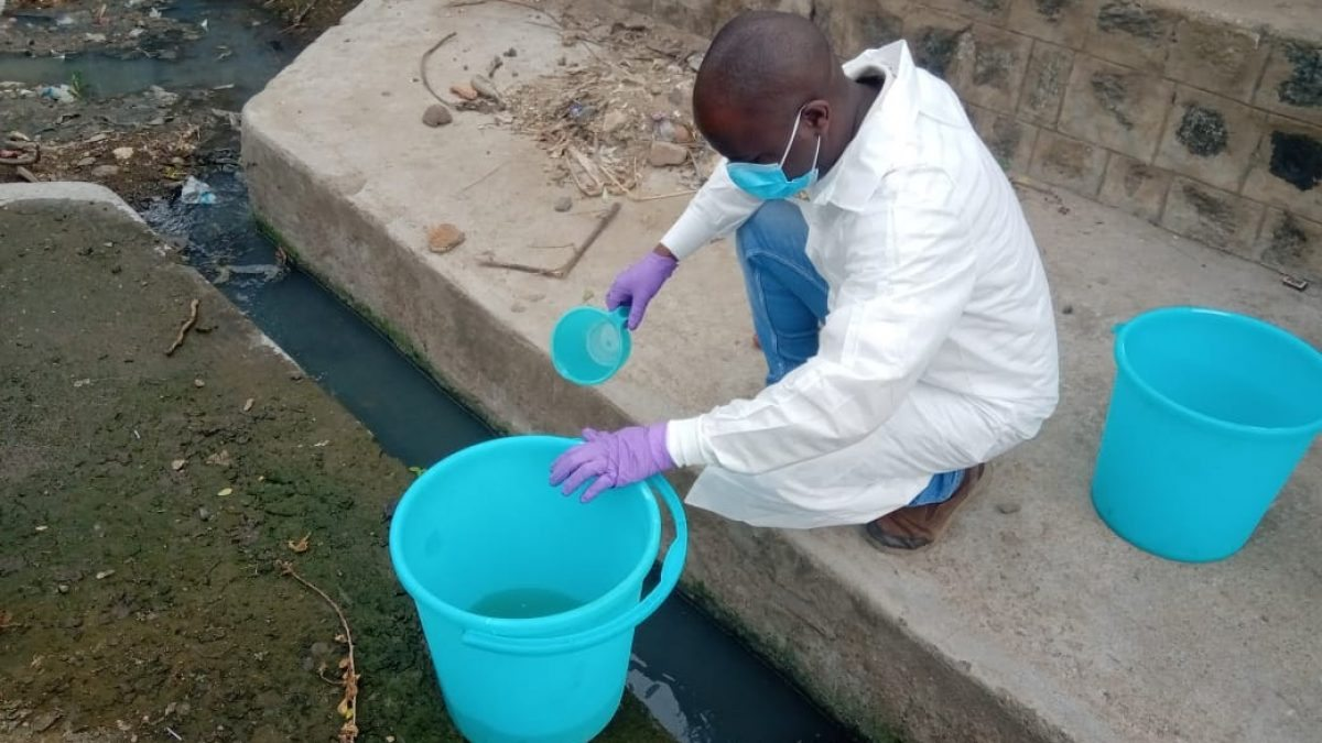 A man pours a water sample into a bucket.