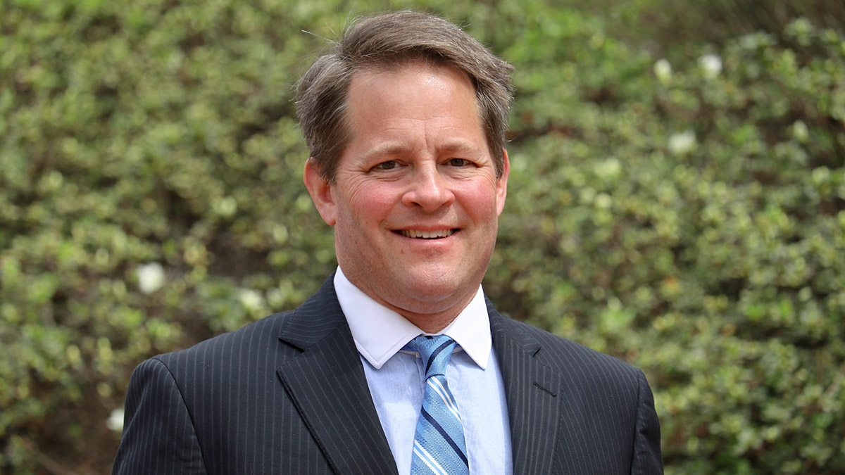 Michael F. Piehler smiles in front of a group of trees.