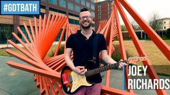 Joey Richards stands outside with a guitar