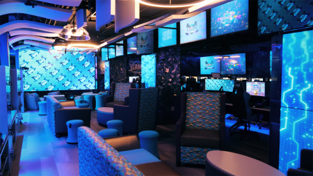 The interior of the Gaming Arena with screens and chairs.