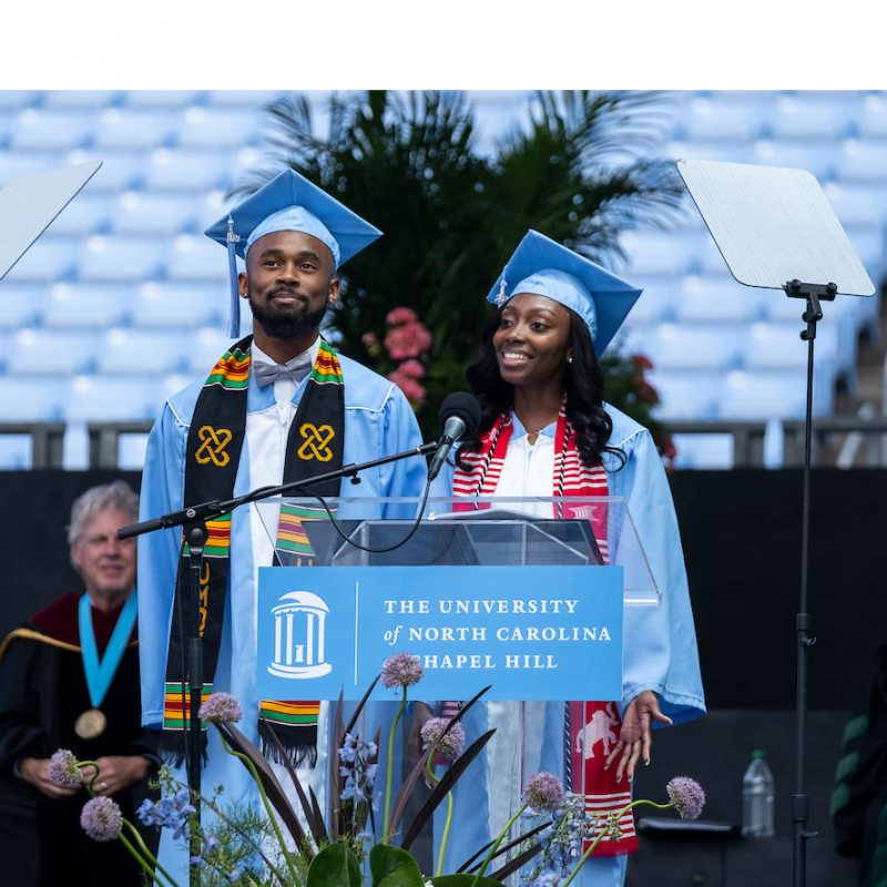 Chris Suggs stands near a podium at commencement.