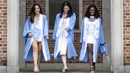 Three graduates walk down the steps of the Bell Tower