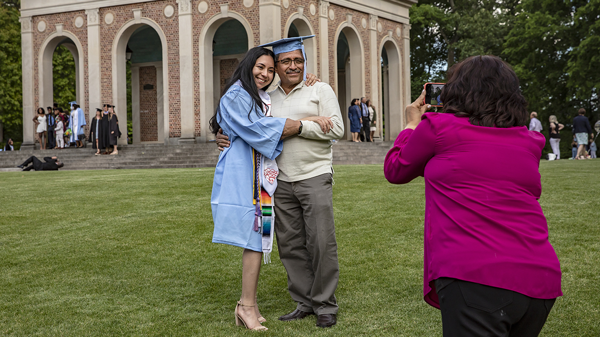 A graduate takes a photo with a family member.