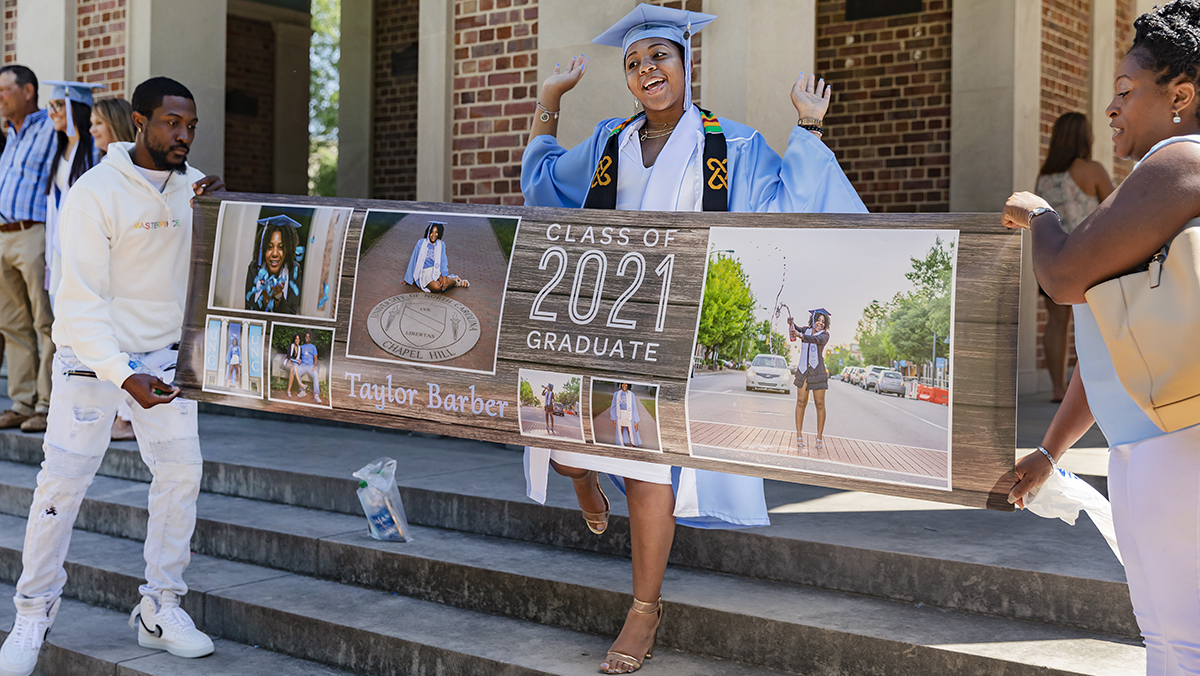 A graduate holds a banner of photos by the bell tower.