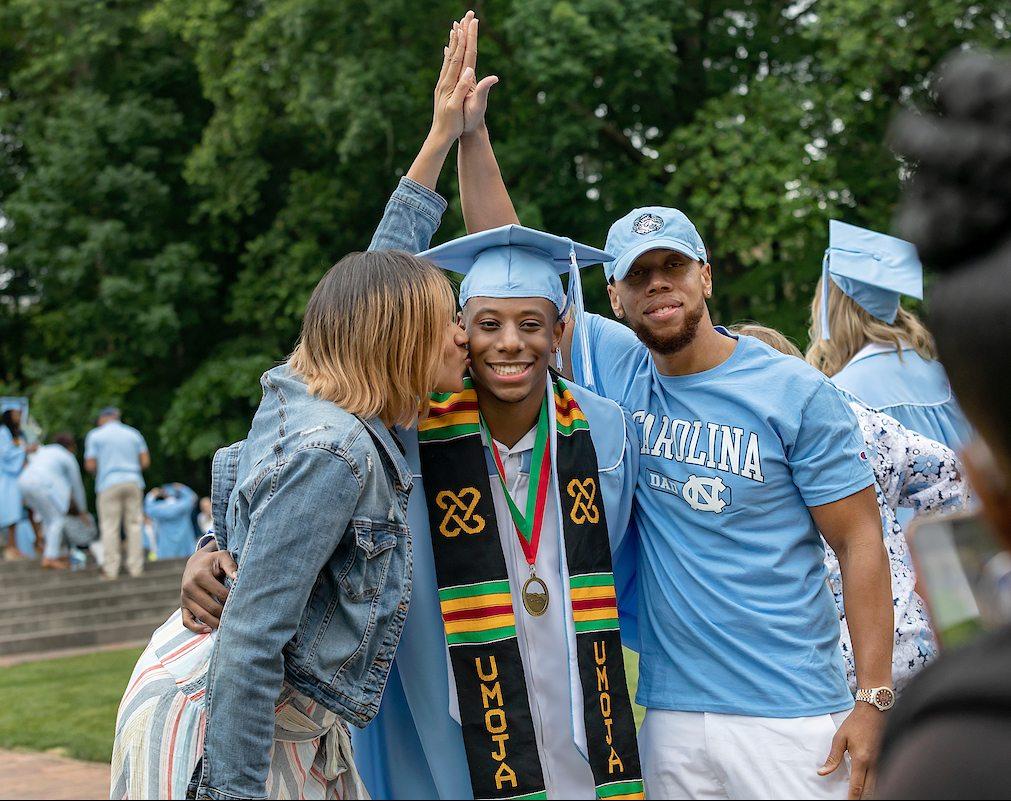 Parents hug their son after graduation.