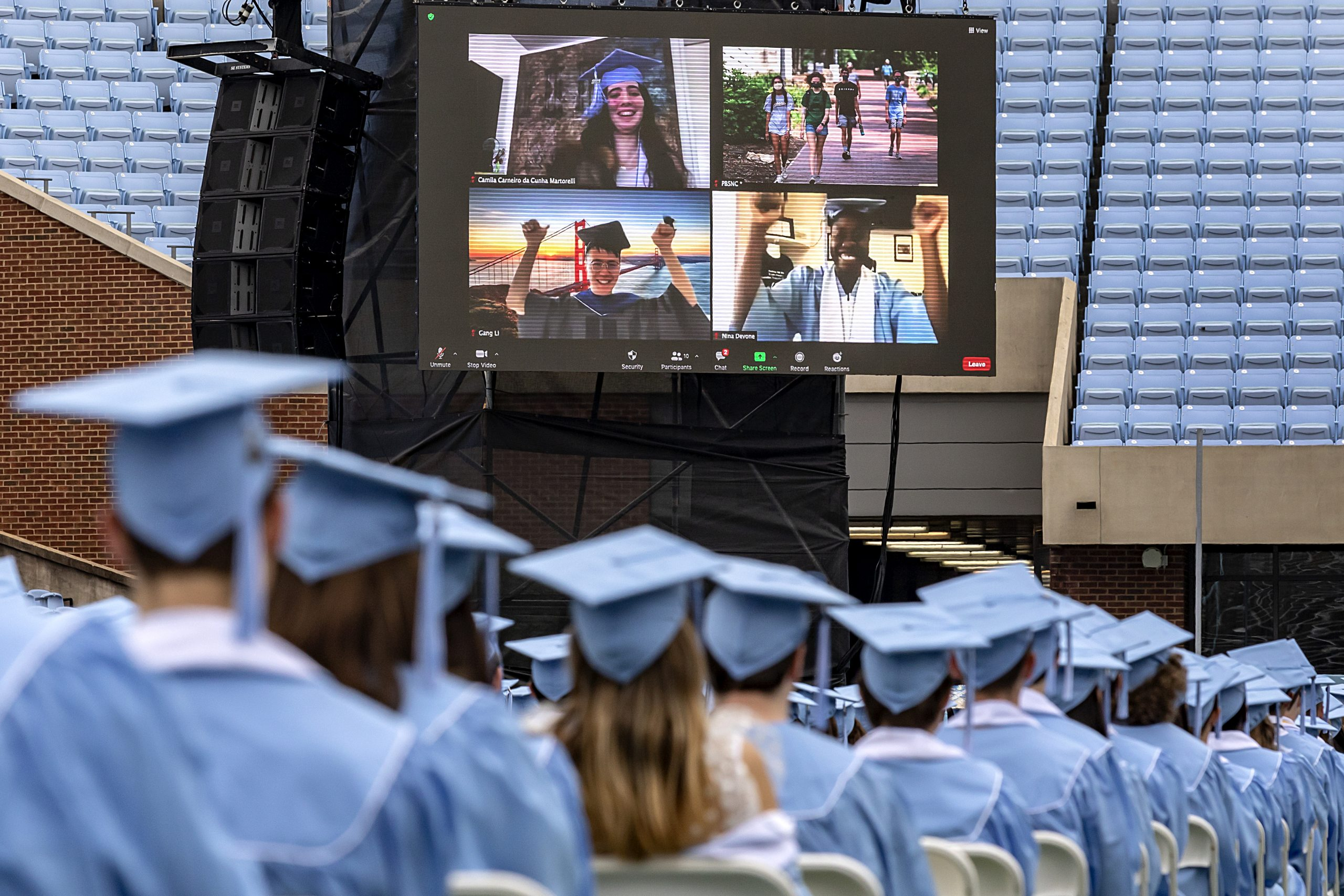Students at sit graduation in Kenan Stadium, with a screen of people on Zoom above them.