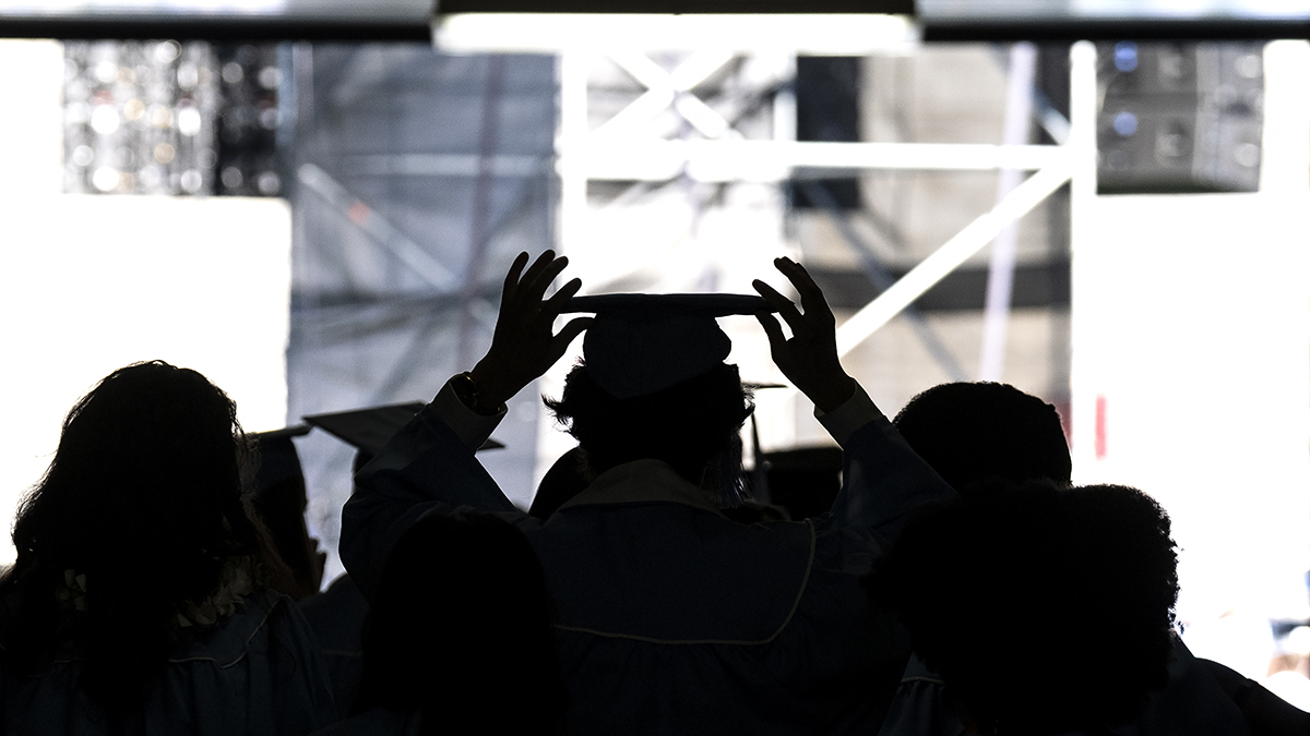 A graduate adjusts their cap while walking out of a tunnel at Kenan Stadium.