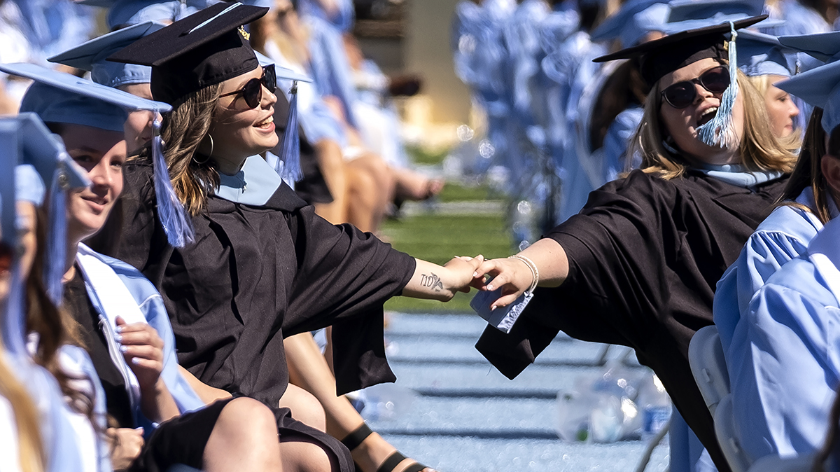 Students fist bump during graduation.