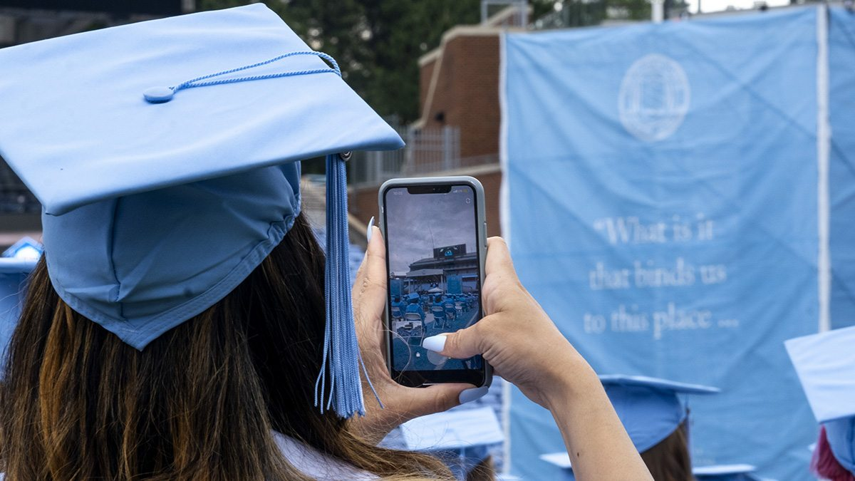 A student takes a photo of the graduation stage.