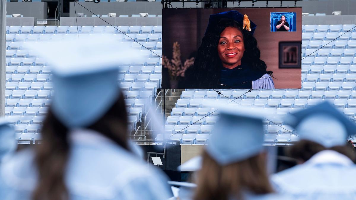 Kizzmekia Corbett is broadcast on a screen while graduates watch.
