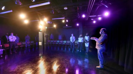 A group of people stand in a performance area in the new facility.