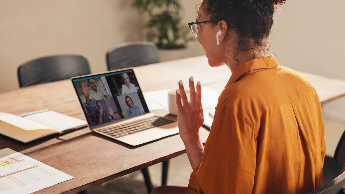 A young woman waves at people joining a video conference call.