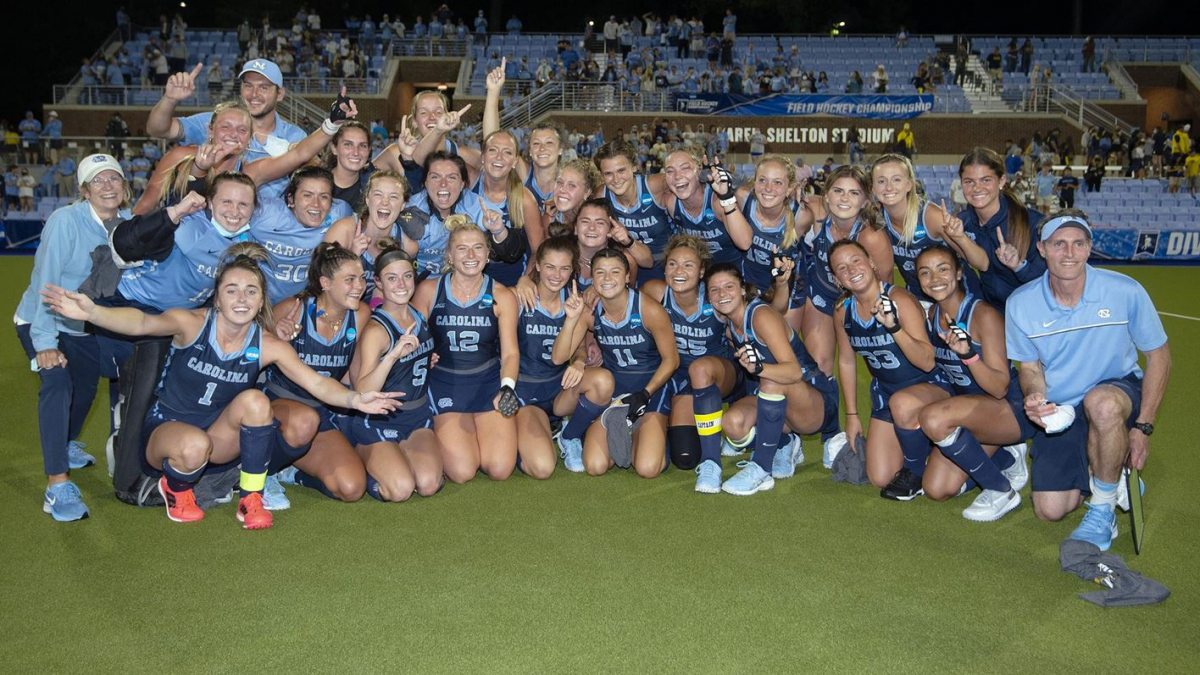 The UNC field hockey team poses for a team photo with the NCAA national championship trophy.
